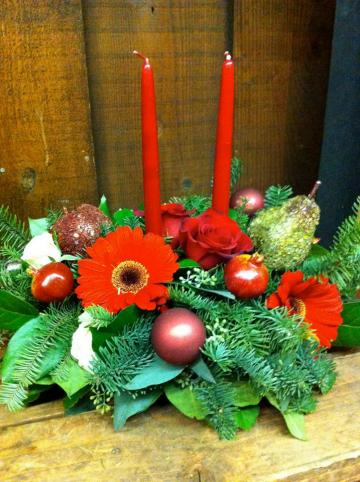 Christmas Centerpiece with ornamental fruit, Gerber daisies, red roses, and a variety of x-mas greens.