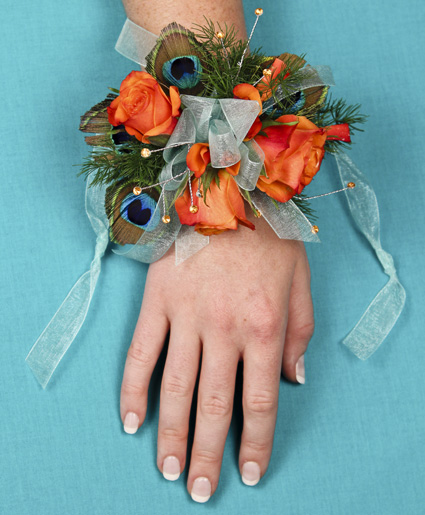 This prom corsage is great with the orange flowers and accents of peacock feathers and blue ribbon.