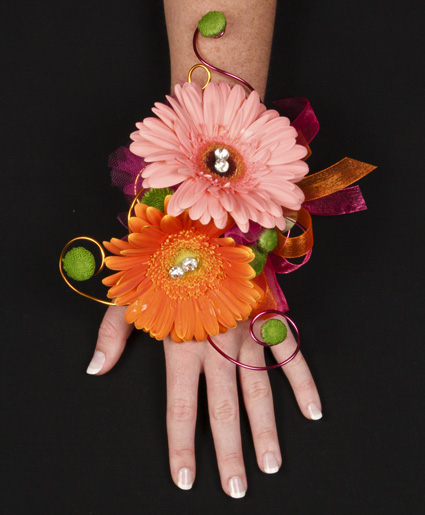 [Image: This pink and orange prom corsage features colorful daisies with hints of wire and crystal accents.]